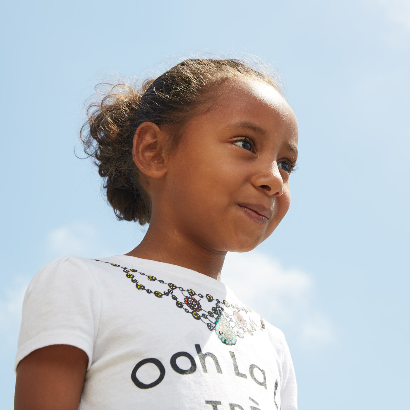 an image taken from a low vantage point of a young girl standing outside with the bright blue sky behind her