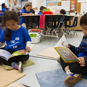 an image of young kids reading books on the classroom floor together
