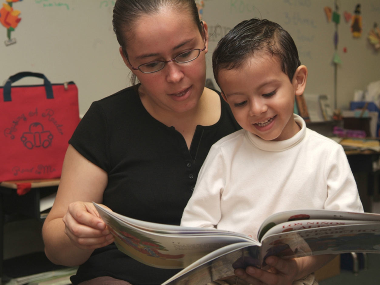 an image of a woman with a small child on her lap while she reads him a book inside their home