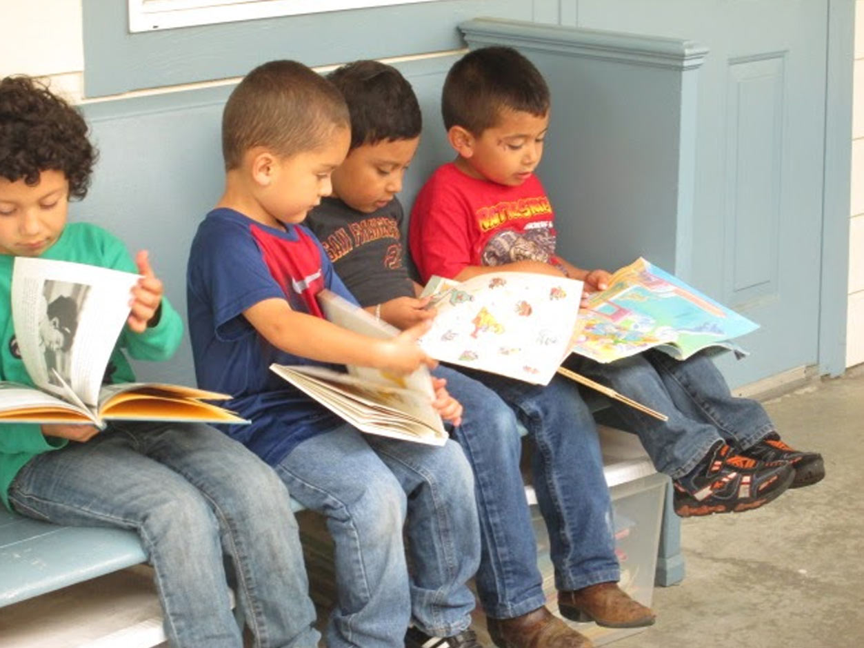 an image of children sitting on a bench reading large childrens books together