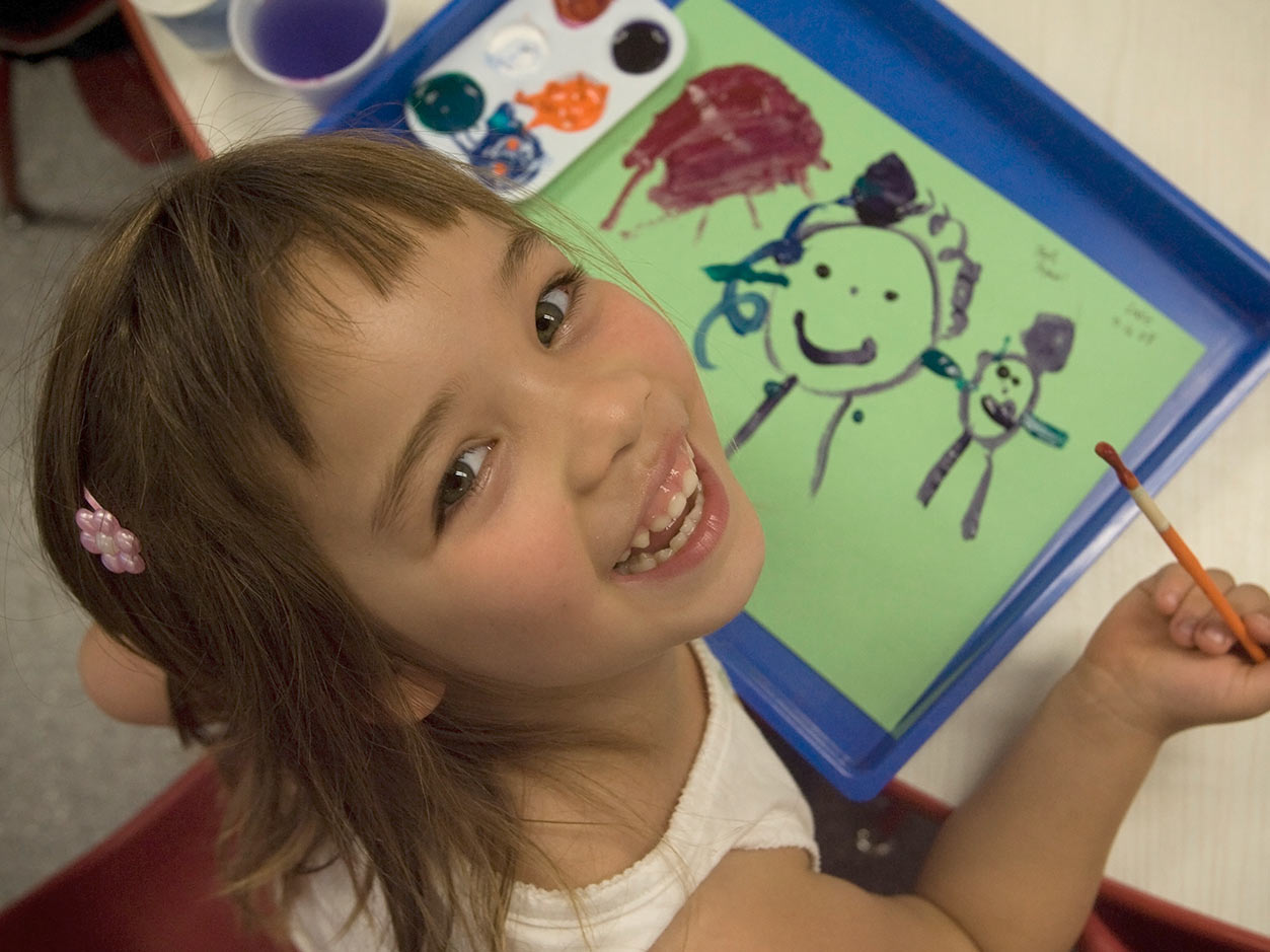 an image of a girl smiling up at the camera with a paint bush in her hand and a painting beneath her hand on the table