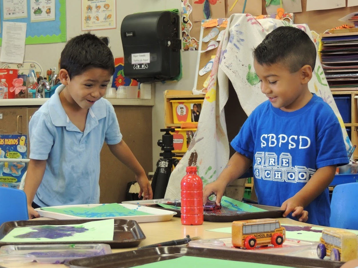 an image of two boys working with art supplies at a desk in a classroom