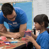 an image of a teacher working closely with a young student